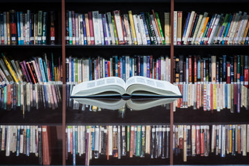 An open book on table front of shelves filled with books