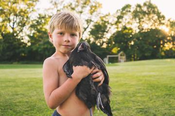 Portrait of a Boy holding q chicken