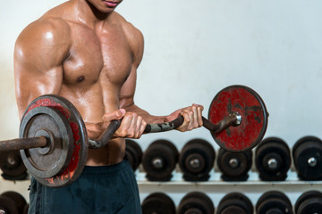 Very power athletic guy bodybuilder , execute exercise with barb