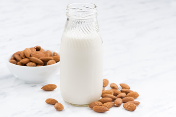 almond milk in a glass bottle on white table, closeup