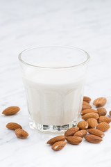almond milk in a glass on white table, closeup