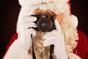 Composite image of portrait of santa taking a photo