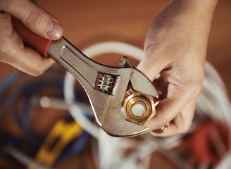 Close-up of plumber hands screwing nut of pipe with wrench over plumbing tools background. Concept of repair and technical assistance.