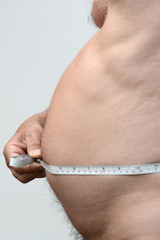 Fat male stomach in profile with tape measure