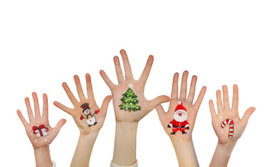 Children's hands raising up with painted Christmas symbols: Santa Claus, Christmas tree, Snow man, present box