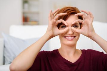 lächelnde frau formt eine brille mit ihren händen