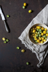 Overhead shot of yellow and green tomatoes on bowl on a rusty table with cloth and knife