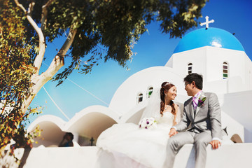 happy stylish asian bride and groom sitting on a wall under gree