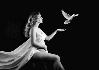 Beautiful pregnant woman produces a white bird from the hand.