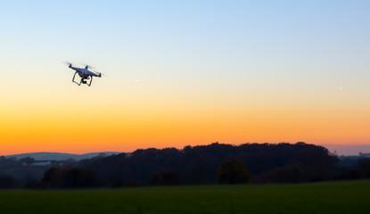 Unbemannte RC Drohne fliegt auf einem freien Feld bei Sonnenuntergang