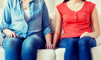 close up of lesbian couple sitting on sofa at home