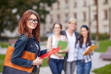 happy teenage students with school folders