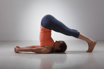 Sporty woman practices yoga asana Halasana