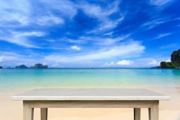 Empty top of natural stone table and view of tropical beach back