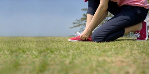 young asian woman tying shoelace