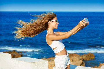 Blond teen girl photo selfie on smartphone at beach