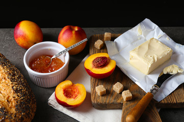 Tasty jam in the bowl, ripe peaches, butter, crackers and fresh bread on wooden tablet close-up