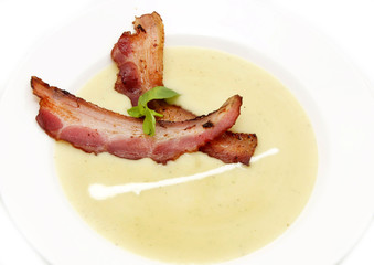 pea soup with bacon on a white plate