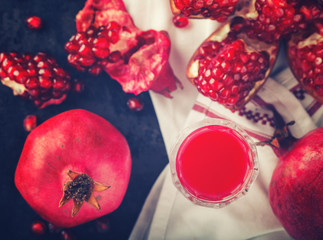 Juicy pomegranates,whole and broken and pomegranate juice . Toned image. Vintage style.selective focus.