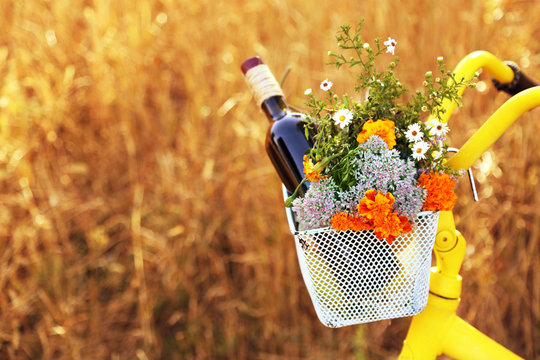 Bicycle with flowers and bottle of wine in metal basket closeup, outdoors