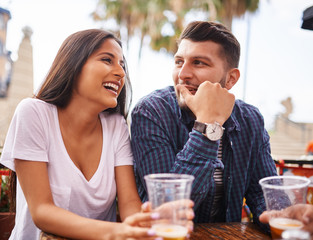 attractive hispanic couple drinking beer and having fun at outdoor restaurant