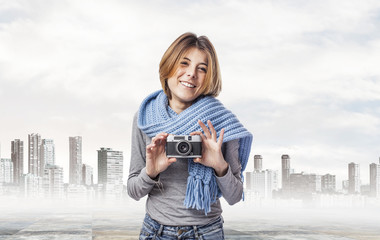 young woman holding a vintage camera at city