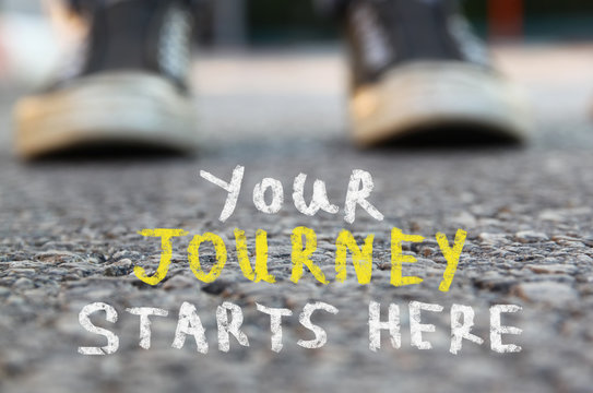 image with selective focus over asphalt road and person sneakers with handwritten text - your journey starts here.  education and motivation concept