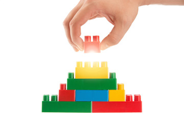 Plastic building blocks and human hand, business conception