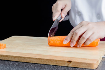 Chef cutting carrot on a wooden board