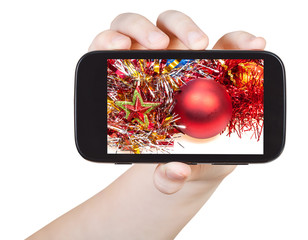 hand holds smartphone with Xmas decorations