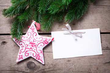 Spruce branches,  Christmas star and empty tag on  vintage  wood