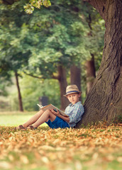 Boy with book sitting under big tree in park
