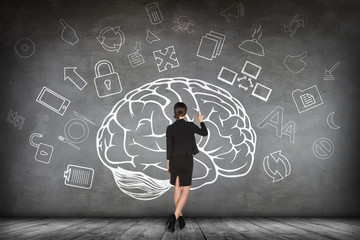 Woman stands beside big drawn brain