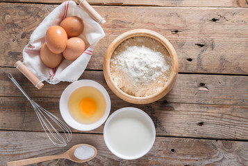 The flour in a wooden bowl, egg, milk and whip for beating.