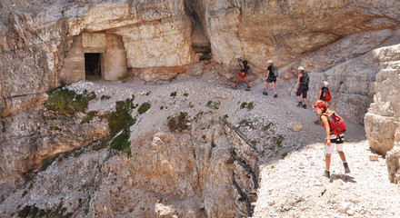Hikers and climbers walking through the tunnel on Via Ferrata, Dolomites, Alps, Italy