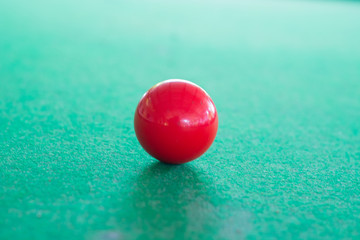 Close up of red snooker ball on the table with green background