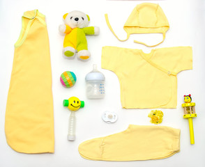 top view of baby girl yellow clothes and toy stuff