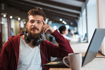 Young confident guy working in office using headset and laptop