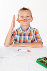 Boy is holding pencil between nose and mouth