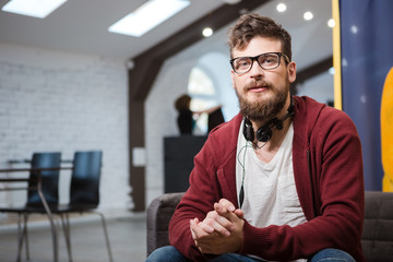 Hipster in glasses with beard sitting on sofa