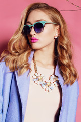 gorgeous woman with blond curly hair in spring outfit: elegant coat, dress and sunglasses