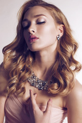 beautiful  woman with blond curly hair wears elegant dress and bijou