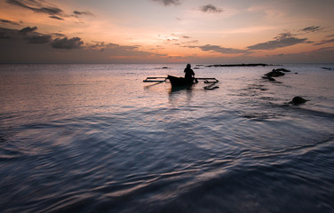 sunset with a traditional fishing boat over Borneo Malaysia