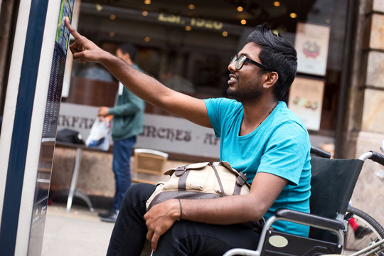 disabled man looking at a street map in his wheelchair.