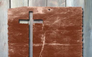 Old vintage Christian paper cross on wood background