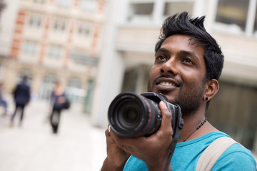 young indian man on holiday taking photos