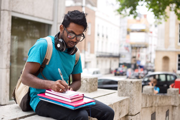 student sitting outdoors writing in a textbook