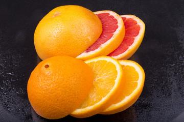 appetizing piece of fresh grapefruit and orange on black backgro