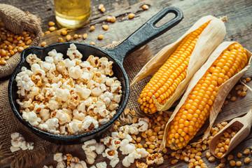 Prepared popcorn in frying pan, corn seeds in bowl and corncobs