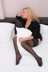 beautiful sexy woman in black stockings and a man's shirt on the bed